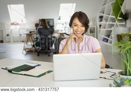Customer Service Assistant Wearing Headset While Sitting Behind Her Computer And Working In The Call