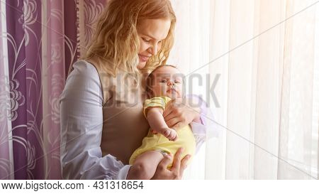 Happy Young Mother With Curly Loose Hair Holds In Arms Baby Girl In Yellow Bodysuit Kissing Near Win