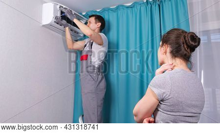Brunette Woman Apartment Owner Watches Electrician Wearing Workwear Removing Of Screws To Open Air C