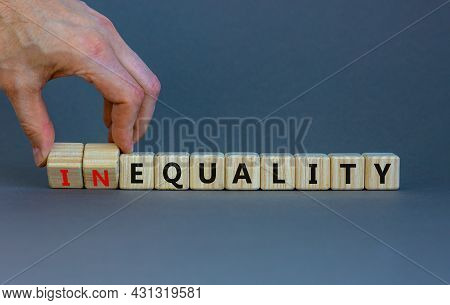 Equality Or Inequality Symbol. Businessman Turns Woden Cubes, Changes The Word Inequality To Equalit