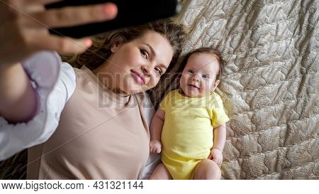 Jolly Young Mother With Plump Lips Takes Picture Of Smiling Baby Daughter In Yellow With Smartphone