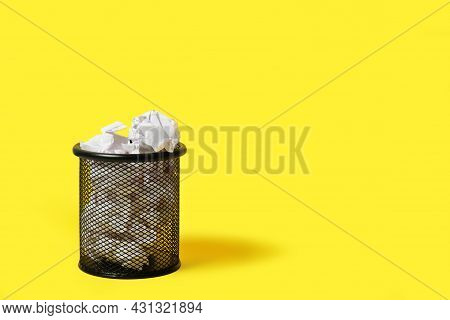 Crumpled Paper In Stationery Wastebasket On Yellow Background