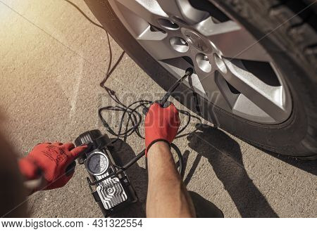Tire Pump Inflating Car Wheel. Tyre Inflator In Male Hands, Top View.