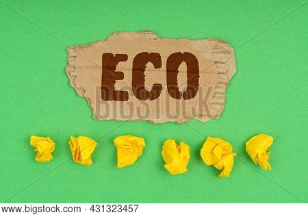 Ecology Concept. On A Green Background, Crumpled Yellow Paper And A Cardboard With The Inscription -