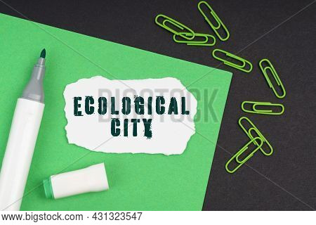 Ecology Concept. On A Black Background, A Marker, Paper Clips, A Sheet And Torn Paper With The Inscr