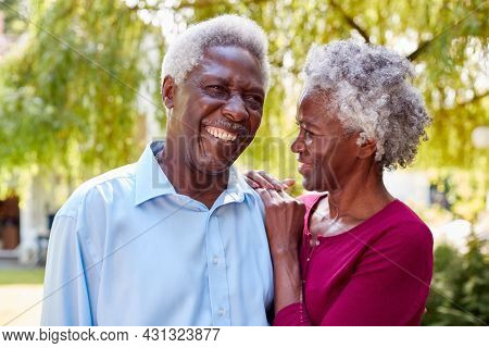 Portrait Of Loving Senior Couple Standing In Garden At Home After Retirement
