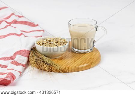 Glass Of Oat Milk With Oat Flakes On White Wooden Background