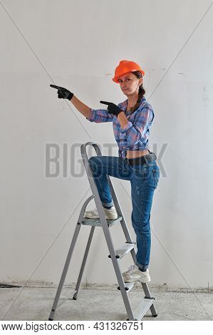 In A Plaid Shirt, A Foreman Sits On A Stepladder
