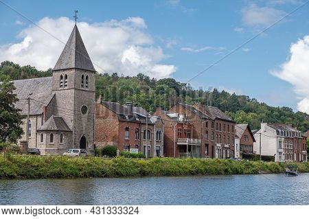 Dinant, Wallonia, Belgium - August 8, 2021: Gray Stone Church Of Neffe Among Other Commom Dwellings