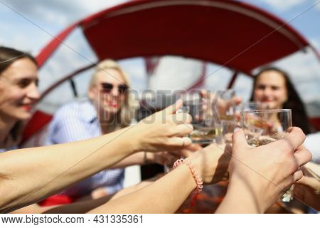Young Women On The Boat Clink Glasses And Laugh
