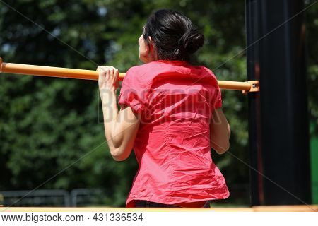 Woman In Shirt Pulls Herself Up On Horizontal Bar