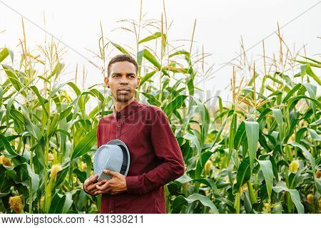 Young Farmer With Hat In The Field With Corn Crops, Hat In Hand