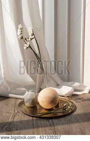 White statice flower in a clear vase on a wooden floor