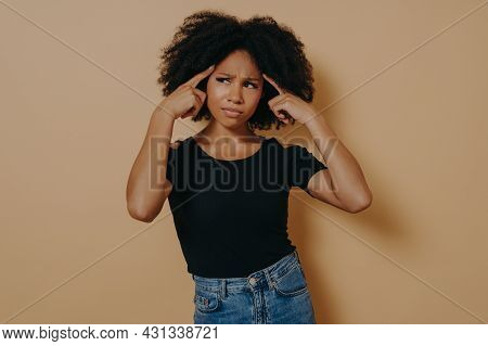 Young Thoughtful Mixed Race Woman With Curly Hair Holds Fingers On Temples And Trying To Concentrate
