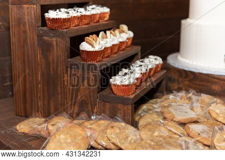 Cupcakes With Frosting And Cookies Wrapped In Plastic Are Arranged On The Dessert Counter.