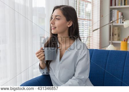 Pretty Young Caucasian Woman Sitting Sofa Look At The Scenery By The Window And Enjoying First Morni