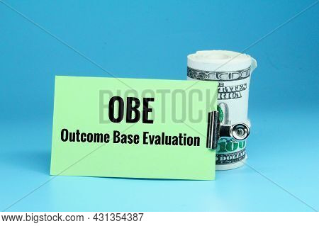 A Roll Of Paper Money And Colored Paper With The Words Outcome Based Evaluation