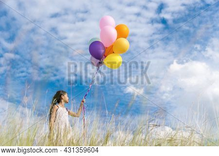 Cheerful Cute Girl Holding Balloons Running On Green Meadow White Cloud And Blue Sky With Happiness.