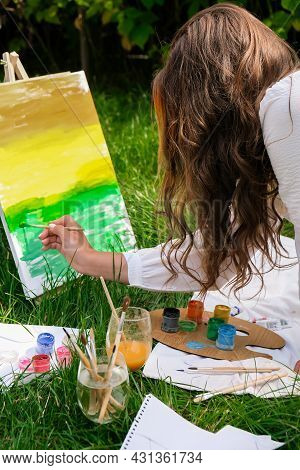 Artist Painting On The Easel Outdoors In The Garden. Open Air Outdoor Art Workshop. Draw On The Canv