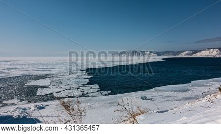 A Non-freezing River Flows Out Of A Frozen Lake. Blue Water And White Ice. Ice Floes Float On The Su