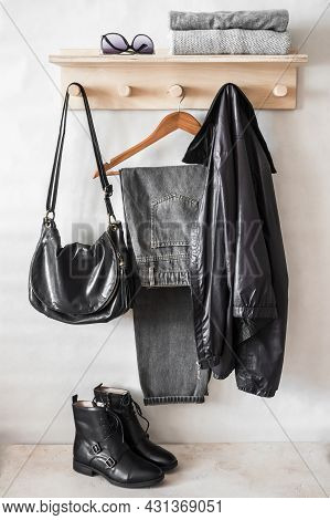 Set Of Autumn Women's Clothing On A Wooden Hanger - Gray Mom's Jeans, A Black Windbreaker, High Leat
