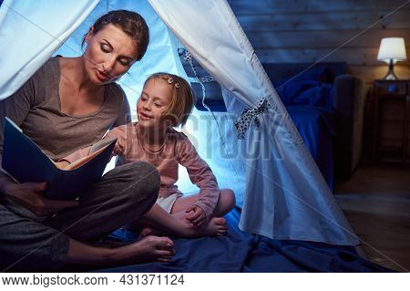 Interested Girl Pointing At Storybook In A Tent On Bed