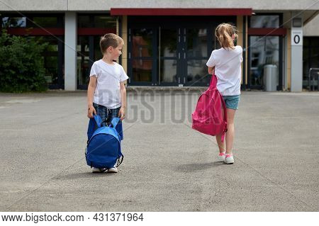 A Boy And A Girl Are Standing With Backpacks In Front Of The School. The Girl Doesnt Want To Go To S