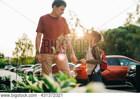 Happy Father And Kid Son Going To Classes. Parent Take Child Boy To School In First Grade. Pupil Of