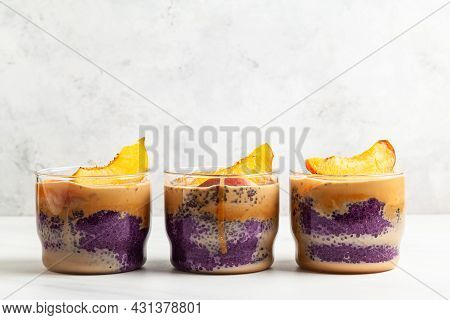 Blueberry Chia Pudding With Caramel And Peaches In Glass Jars On A White Table.