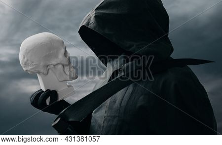 The Grim Reaper Stands With A Scythe In The Background Of The Dark Sky And Looks At The Skull.