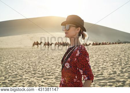 Asian Woman In Red Dress Looking At View In Desert With Caravan Of Camels And Huge Sand Dunes In Bac