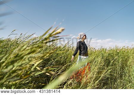 Asian Woman Enjoying Fresh Air And Sunlight In A Field Of Reeds