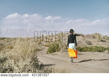 Rear View Of An Asian Woman In Long Skirt Walking On A Dirt Road Through Gobi Desert