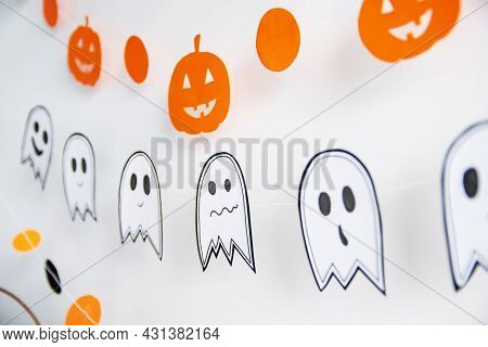 Festive Decor On The White Wall Garland Paper In The Form Of A Pumpkin, Ghost. Halloween Holiday Dec
