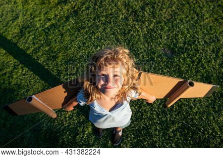 Funny Child Boy Flying In Plane Made Craft Of Cardboard Wings. Dream, Imagination, Childhood. Travel