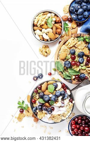 Sugarless Muesli In Bowl And Ingredients For Healthy Breakfast. Granola, Nuts, Blueberry, Cranberry,