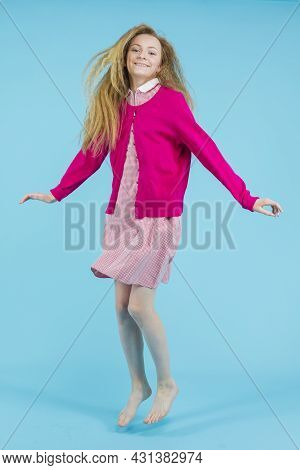Teens Lifestyle. Active Teenage Girl In Red Checked Dress With Pink Jumper Moving In Jump Against Bl
