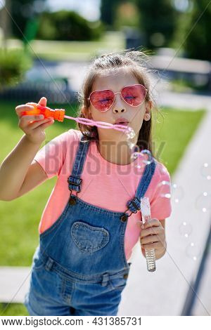 Child Girl Blowing Soap Bubbles In Park.