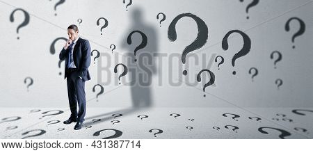 Thoughtful Young European Business Man Standing In Concete Interior With Question Mark Sketch. Solut
