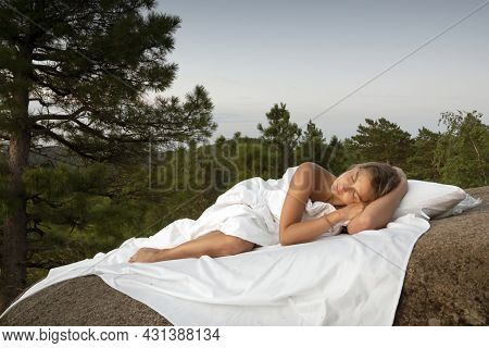 A Young Girl Woman Sleeps On A White Sheet In The Forest On The Rocks Of The Bark In Bed, Close-up.