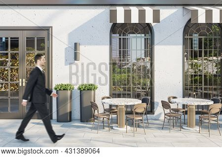Young Man In Suit Walking Past Creative Concrete Cafe Exterior With Terrace Furniture In Daylight