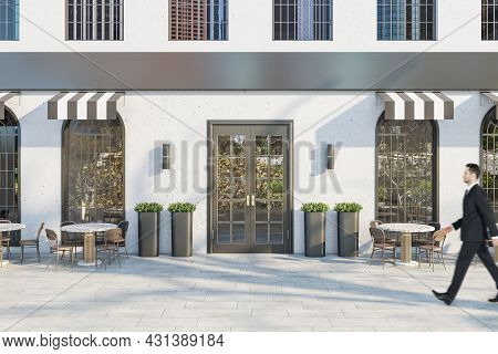 Young Businessman In Suit Walking Past Creative Concrete Cafe Exterior With Terrace Furniture In Day