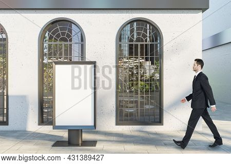 Businessman Walking Past Creative Business Center Exterior With Empty Mock Up Frame Stand, Windows A
