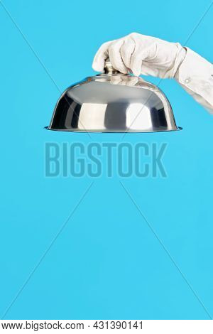 Elegant Waiters Hand In White Glove Holding Metal Cloche Lid Cover On Blue Background
