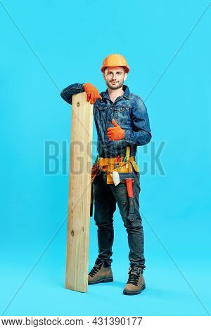 Full Length Portrait Of Young Handsome Carpenter Showing Thumbs Up Sign Holding Pile Of Lumber Woods