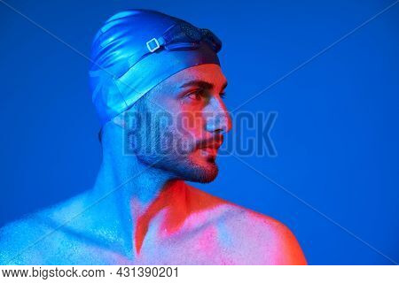 Close Up Profile Portrait Of Handsome Swimmer With Goggles In Red-pink Neon Light Over Blue Backgrou