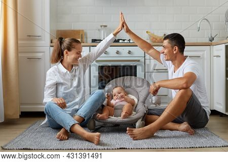 Full Size Photo Of Positive, Three People Mommy Daddy Small Kid Girl Or Boy In Bouncer, Parents Make