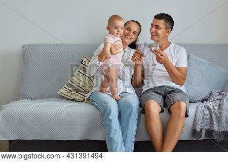 Indoor Shot Of Happy Family Mother, Father, Child Baby Daughter At Home On The Sofa Playing And Laug