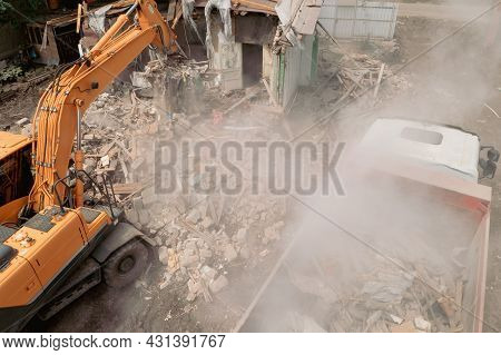 Demolition Of House Building For New Construction. Excavator Bucket Load Garbage Into Truck, Aerial