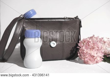 White Plastic Bottle Next To Handbag And Flowers. Collagen Or Protein Drink To Go. Liquid Protein Fo